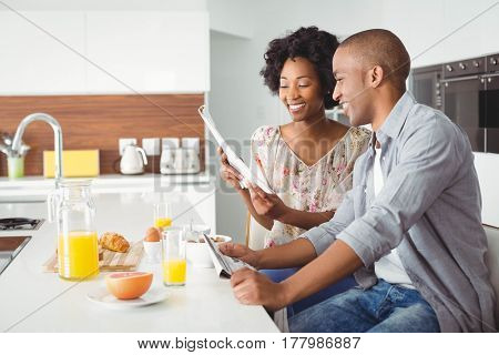 Smiling couple reading and eating breakfast together in the kitchen at home