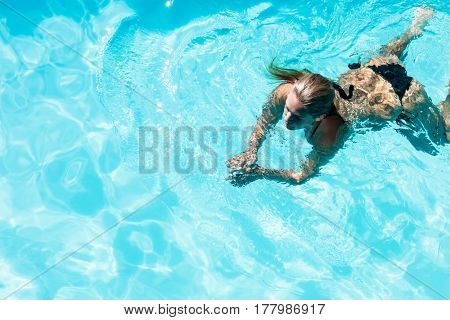 Fit woman swimming in the pool in a sunny day