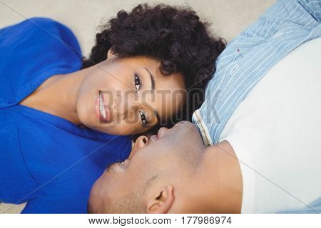 Peaceful couple lying on the floor face to face
