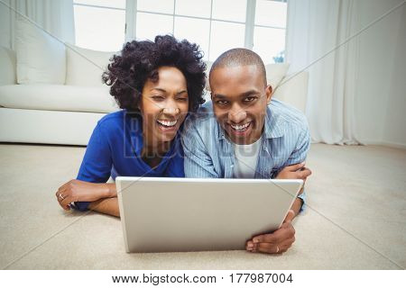 Smiling couple lying on the floor and using laptop