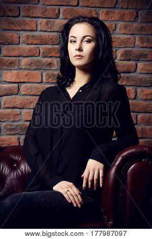 Beautiful dreamy girl sitting on a sofa. Beauty, fashion. Natural make-up, cosmetics.