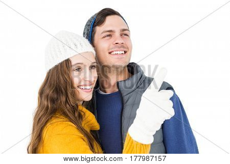 Smiling couple pointing and looking away on white background