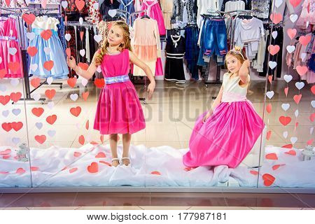 Two cute little girls in beautiful dresses posing in the window of children's clothing store. Kid's fashion. Seasonal sale and shopping.
