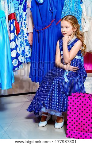 Pretty little girl child choosing a new dress in the shop of children's clothes. Seasonal sale and shopping. Kid's fashion.