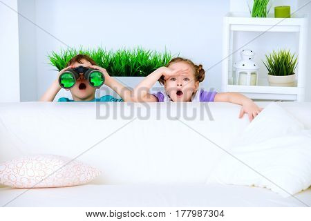 Two funny children playing war together at home.