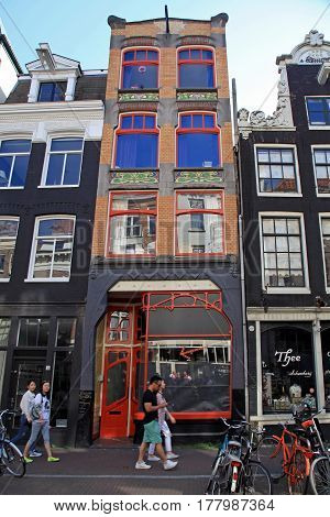 AMSTERDAM, NETHERLANDS - MAY 8, 2016: A typical Amsterdam street with old dutch buildings and tourists in Old Town of Amsterdam, Netherlands.