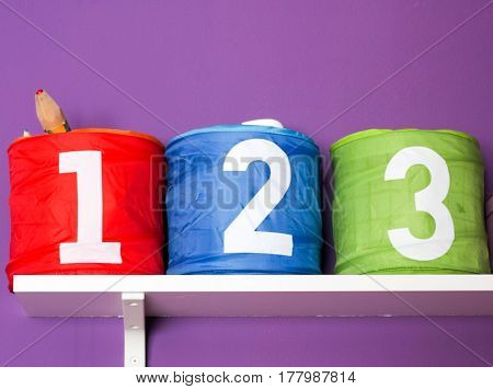 Colorful Boxes For Toys For Children Room On Purple Wall With Numbers: One, Two, Three Close Up Deta
