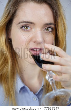 Portrait of young a caucasian white woman while she is drinking wine. She is blonde and pretty with light brown eyes. The background of the image is white.