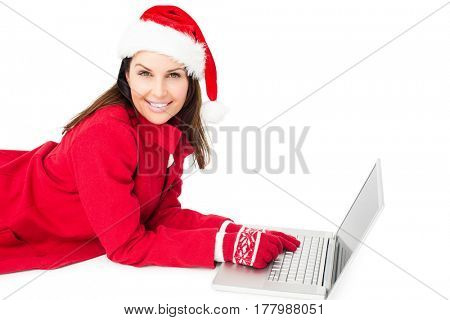 Brunette with santa hat lying on the floor using her laptop on white background