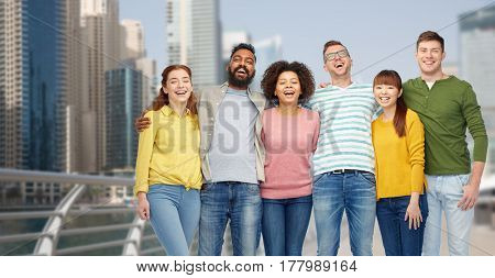 diversity, travel, tourism and people concept - international group of happy smiling men and women over dubai city background