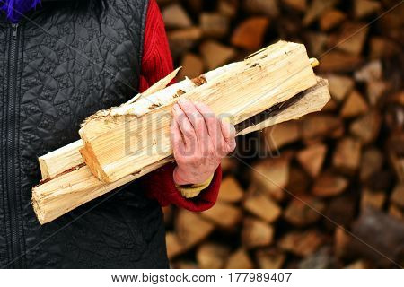 Old woman with firewood in the hands in the village.