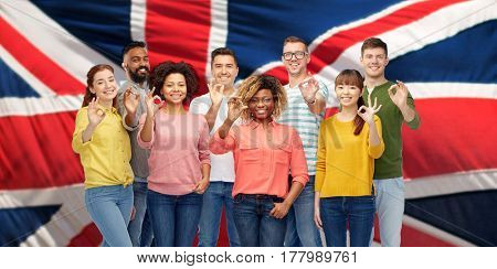 diversity, race, ethnicity and people concept - international group of happy smiling men and women showing ok hand sign over british or english flag background