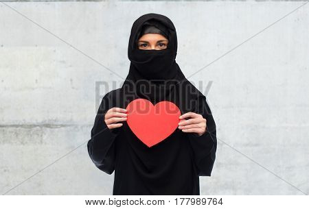 love, charity, valentines day and people concept - muslim woman in hijab holding red heart over gray concrete wall background