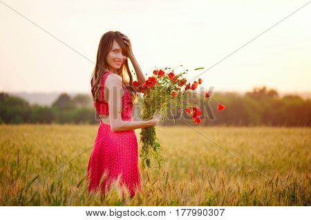 Beautiful Woman With Bouquet Of Poppies In A Wheat Field