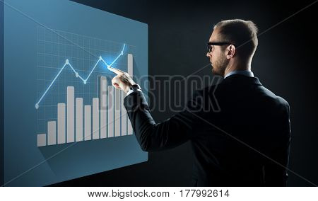 business, people, technology and statistics concept - businessman in suit and glasses pointing finger to virtual screen with diagram chart over black background