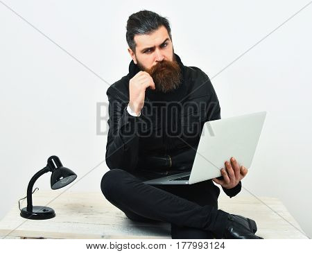Bearded Brutal Caucasian Hipster Sitting On Table With Laptop