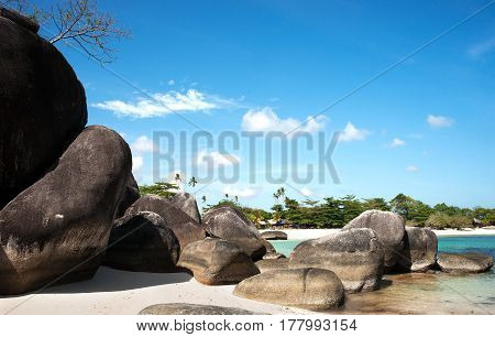 Natural rock formation on white sand beach shore in the afternoon and a white sand beach with palm trees at the background in Belitung Island Indonesia.