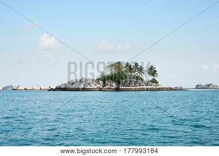 Natural rock formation in sea with green palm trees and vegetation on top at Belitung Island in the afternoon and a white lighthouse at the background Indonesia.