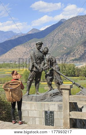 Shigu, China - March 17, 2017: Naxi Woman In Front Of A Statue Celebrating The Red Army Of China In