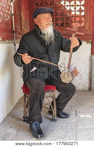 Shigu, China - March 17, 2017: Old Blind Chinese Man Playing Ancient Chinese Stringed Instrument In