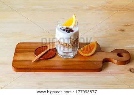 focus glass the dried cereal with yogurt Parfait and orange. The symbol of healthy nutrition put on the wood background Healthy eating concept.