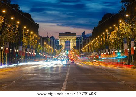 Night view of Paris traffic in Champs-Elysees street and the Arc de Triomphe in Paris France.