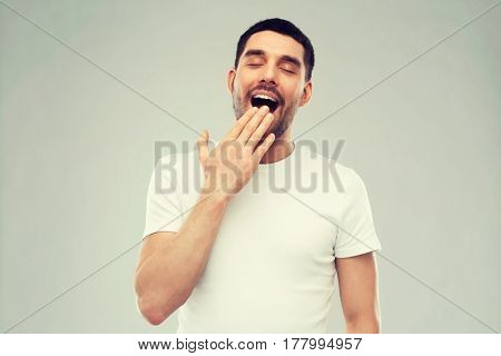 rest, bedtime and people concept - tired yawning man over gray background