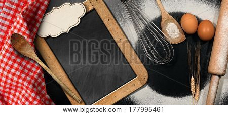 Baking background with empty blackboard and label on a black table with rolling pin whisk eggs spoons ears of wheat and a checkered tablecloth