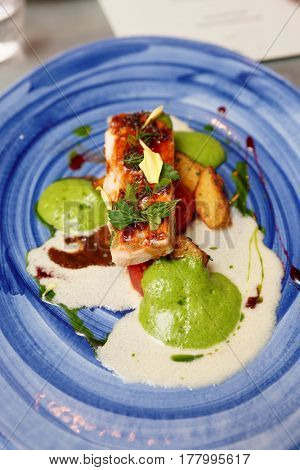 Chicken fillet with creamy and herbal sauce on blue clay plate