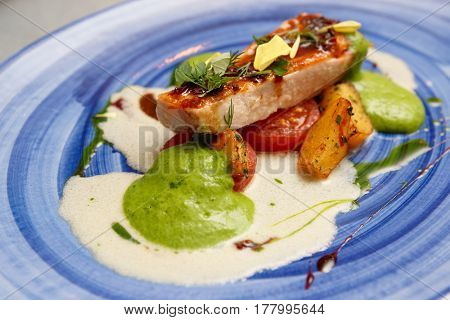Chicken fillet steak with sauces and baked potatoes on blue porcelain plate