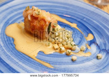 Chicken roll with spinach and stewed celery on blue clay plate