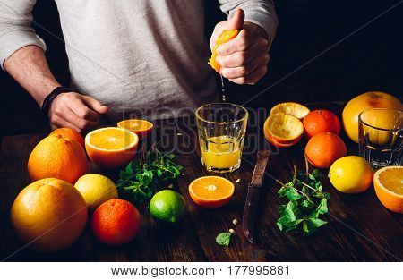 Guy Prepare the Citrus Cocktail. Glass of Juice Fruits and Mint on Table.