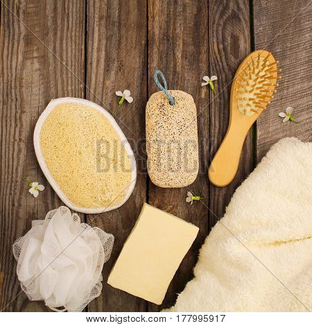 Hygiene products: soap, towel, comb, sponge, pumice stone, flowers on the table. Top view.