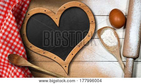 Baking background with empty blackboard in the shape of a heart on a wooden table with flour egg rolling pin spoons and checkered tablecloth