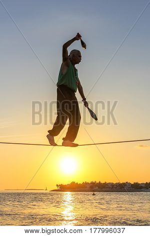 Key West, Florida, United States - April 13, 2012: a tightrope walker performs during the Sunset Celebration at Mallory Square. Show of street artists is one of most popular attractions of Key West.