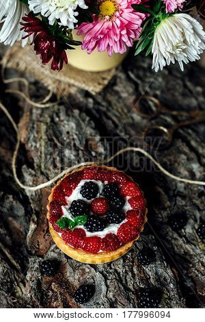 homemade Tart with berries with flowers on rustic background
