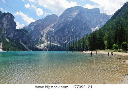 BRAIESIT - CIRCA JULY 2015 - Tourists bath in Braies Lake in the Dolomites. Braies lake is one of the highest lakes in the Alps.