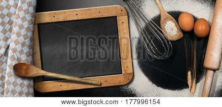 Baking background with empty blackboard on a black table with Rolling pin whisk eggs spoons ears of wheat and a brown and white checkered tablecloth