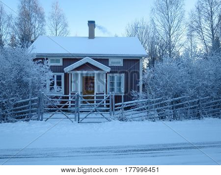 A cute red cabin in Sweden during winter.