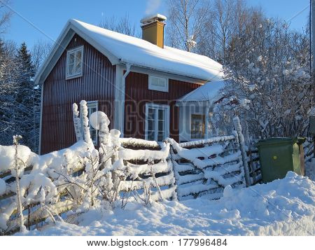 A red cozy cabin in a wintery Sweden.