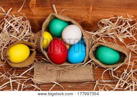 Painted Easter Colorful Eggs In Burlap Sack On Wooden Background