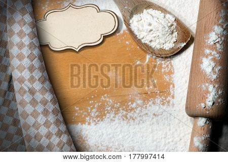 Rolling pin and a spoon with white flour on a wooden table with an empty label with copy space and a brown and white checkered tablecloth