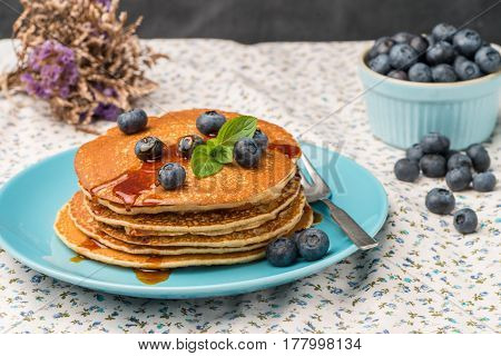Delicious golden pancakes with fresh black berries.