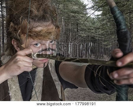 Portrait image of a teenage tribal warrior with a bow and arrow. With a woodland background.