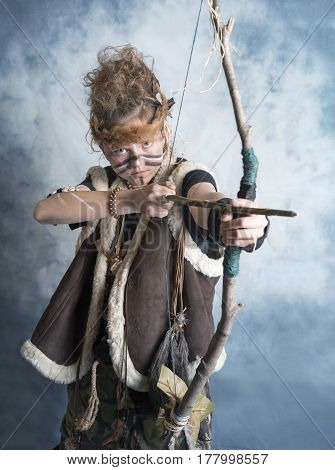 Portrait image of a teenage tribal warrior with a bow and arrow. Taken on a blue background.
