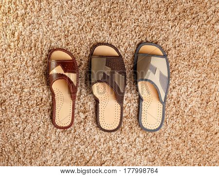 Three different sized slippers stand on a fleecy carpet. View from above