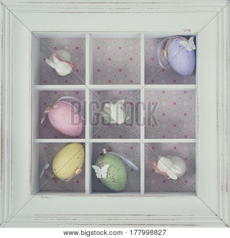 Easter tic tac toe game with eggs and rabbits in box clos eup - pastel colors and rustic style, retro toned