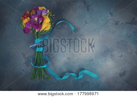 Mix of fresh freesia flowers on gray stone background with copy space, retro toned