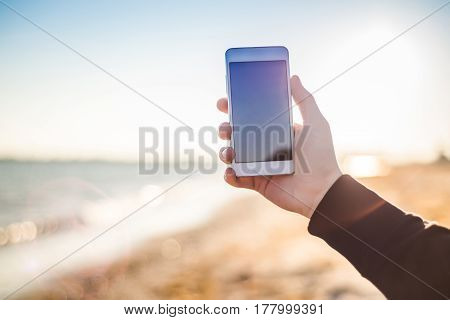The hand is holding the phone in the sun. Close-up