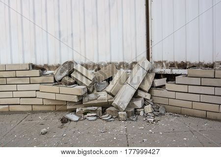 Closeup image of damaged obsolete structure of grey bricks with metal door above it